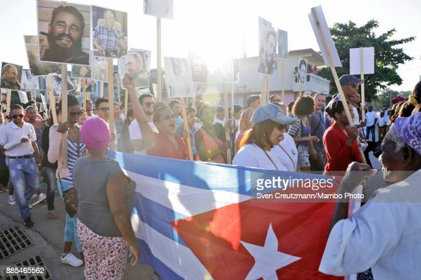 Cuban carry photos of late Cuban Revolution leader Fidel Castro during a march from the Revolution square to the Santa Ifigenia cemetery as Cuba...