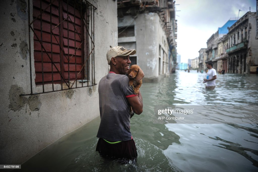 Cuban carrying his pet wades through a flooded street in Havana, on September 10, 2017. Deadly Hurricane Irma battered central Cuba on Saturday, knocking down power lines, uprooting trees and ripping the roofs off homes as it headed towards Florida. Authorities said they had evacuated more than a million people as a precaution, including about 4,000 in the capital. /