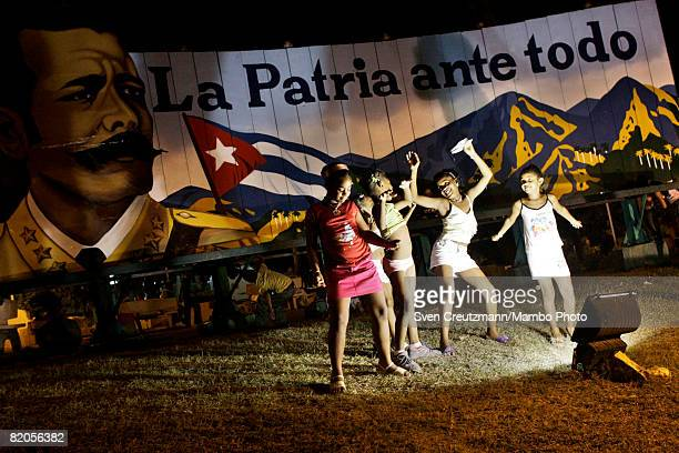 Cuban children dance in front of a political propaganda sign showing the image of Antonio Maceo leader of Cuba's independence war against Spain in...
