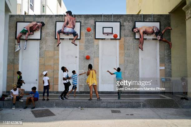 Cuban children play basketball at an art installation by Spanish artist Martin y Sicilia at the Malecon waterfront during the 13th Havana Biennial...