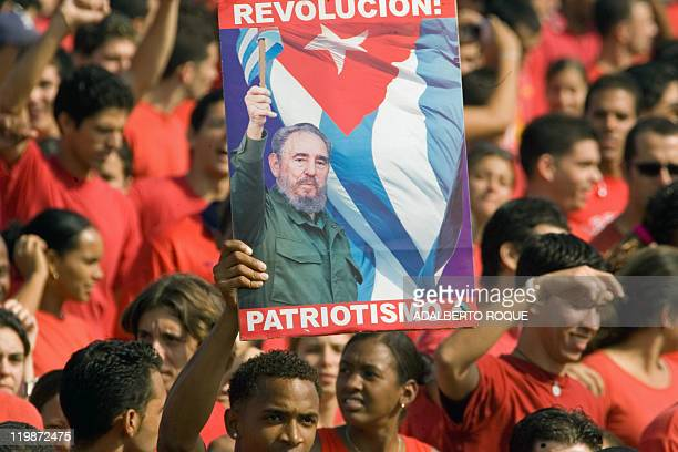 A Cuban citizen holds a poster of Cuban President Fidel Castro during the May Day parade in the Revolution Square in Havana 01 May 2007 Cuban...