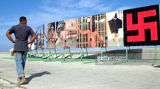 A Cuban citizen walks past enormous posters of US soldiers torturing Iraqi prisoners at the Abu Ghraib prison Posters are spread across the street in...