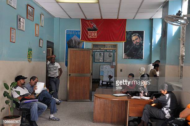 A Cuban Communist Party flag hangs on a wall of an office in Havana next to a portrait of Cuban former President Fidel Castro on November 9 2010...