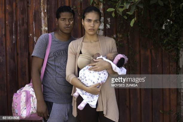 Cuban couple Elaine Miranda Perez and Marcos Delgado Perez hold their onemonthold daughter while waiting outside the National Immigration Institute...