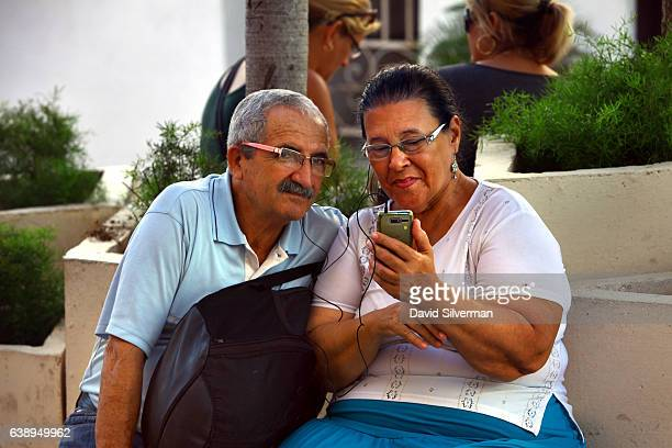 Cuban couple uses their mobile phone to make a video call at a WiFi spot on December 23 2015 in Cienfuegos Cuba In June 2015 the Cuban state...