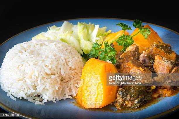 Cuban Cuisine lamb stew in tomato sauce with potatoeswhite rice and salad as side plates