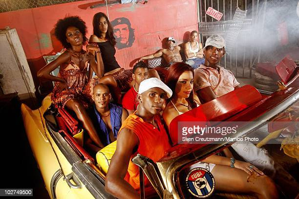 Cuban dancers of the KINGS OF SALSA, a show by british theater director Jon Lee, sit in an Cadillac 1950 during a photoshoot in a garage against the...