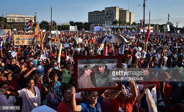 A Cuban displays a picture showing Cuban former president Fidel Castro and president Raul Castro during the May Day parade in Havana on May 1 2016 /...