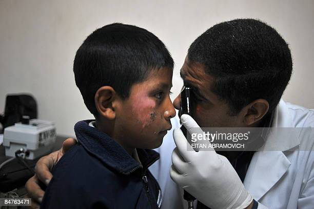 Cuban doctor Davil Ferrer checks the eyes of a boy in the village of San Mateo in Antigua on February 12 2009 Hundreds of indigenous residents of a...