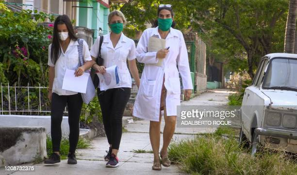 Cuban doctor Liz Caballero from El Vedado polyclinic in Havana walks with two students as they go door by door looking for possible cases of the...