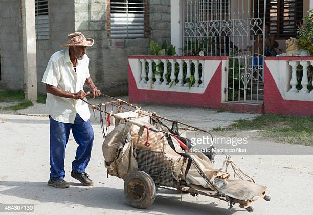Cuban everyday scenes Old senior with homemade wheelbarrow collecting aluminum cans through the city neighborhood They exchange the cans for money in...