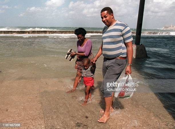 A Cuban family walks through the flooded Malecon in Havana 04 February High tides high winds and heavy rains have affected the island after a...