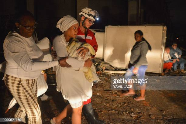 A Cuban firefighter assists a mother and her baby during evacuations in the tornadohit Luyano neighborhood in Havana early on January 28 2019 A rare...
