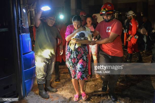 Cuban firefighters assist the evacuation of a mother and her baby in the tornadohit Luyano neighborhood in Havana early on January 28 2019 A rare and...