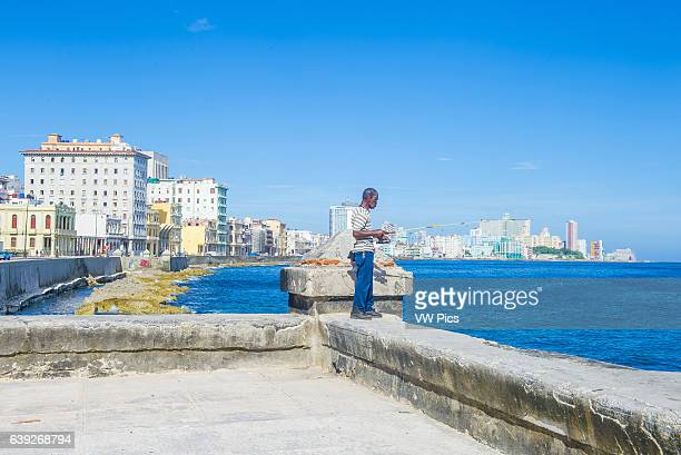 Cuban fisherman at the seafront wall of the Malecon in Havana The historic center of Havana is UNESCO World Heritage Site since 1982