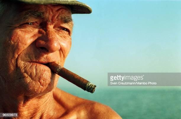 Cuban fisherman smokes a Cuban cigar during a fishing trip offshore the little fishermen village Cojimar on June 13 in Havana Cuba The American...