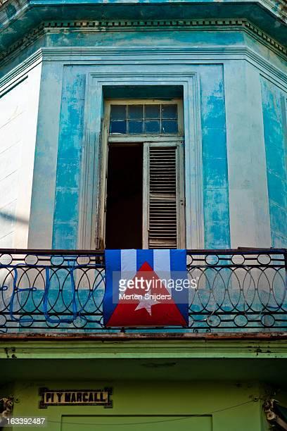 cuban flag hanging over balcony fence - merten snijders stockfoto's en -beelden
