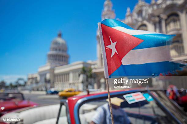 cuban flag in motion against capitolio - cuba foto e immagini stock