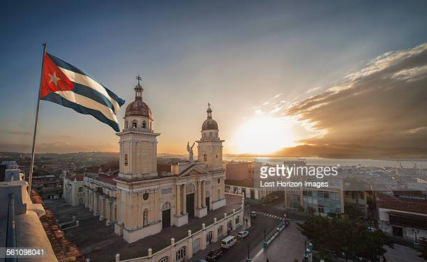 cuban flag over plaza de la cathedral at sunset, santiago de cuba, cuba - cuba foto e immagini stock