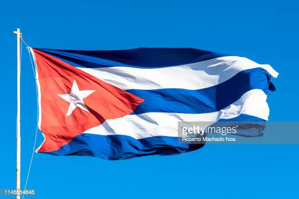 Cuban flag waving in the wind during a blue clear sky day The patriotic symbols has a red triangle with a white star in the center Also three blue...