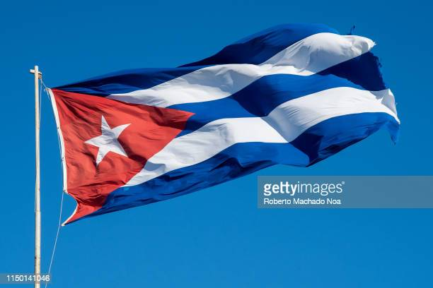 Cuban flag waving in the wind during a blue clear sky day The patriotic symbol has a red triangle with a white star in the center Also three blue...