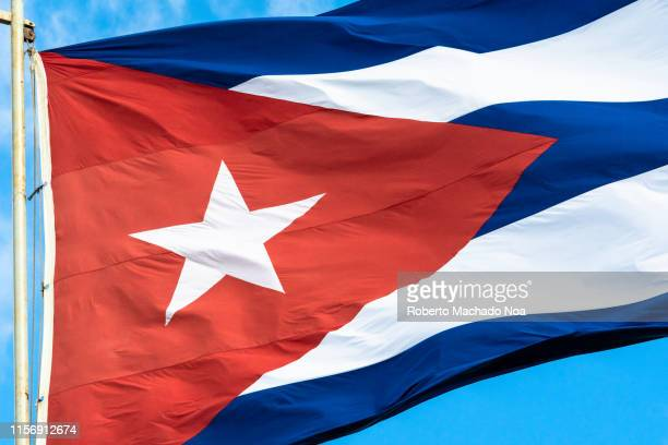 cuban flag waving on a blue clear sky day - cuban flag stock pictures, royalty-free photos & images