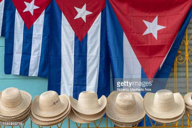 Cuban flags of different sizes and straw hats being sold as tourist souvenirs in the porch of a colonial style private house