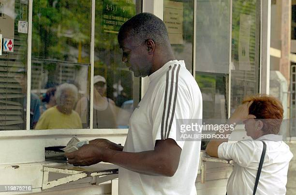 A Cuban gets Cuban Pesos for his US dollars 28 October 2004 in Havana Cuban President Fidel Castro announced in a speech late Monday that US dollars...