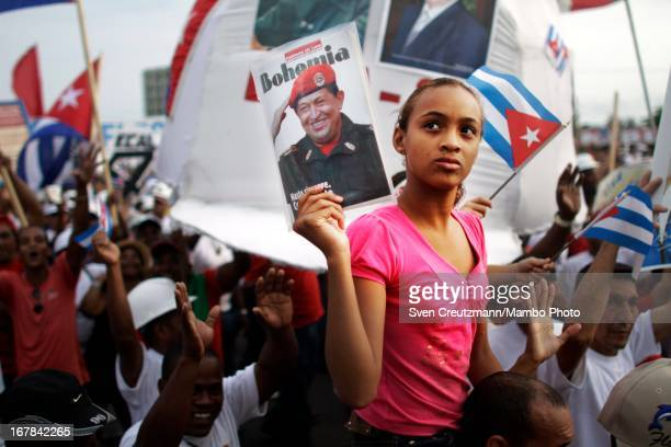 Cuban girl holds up a photo of the late Venezuelan President Hugo Chavez during the annual May Day parade of hundreds of Cubans at the Revolution...