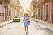 Cuban girl looking at mobile phone, walking down street in Havana