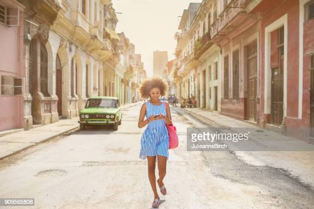 Cuban girl looking at mobile phone, walking down street in Havana