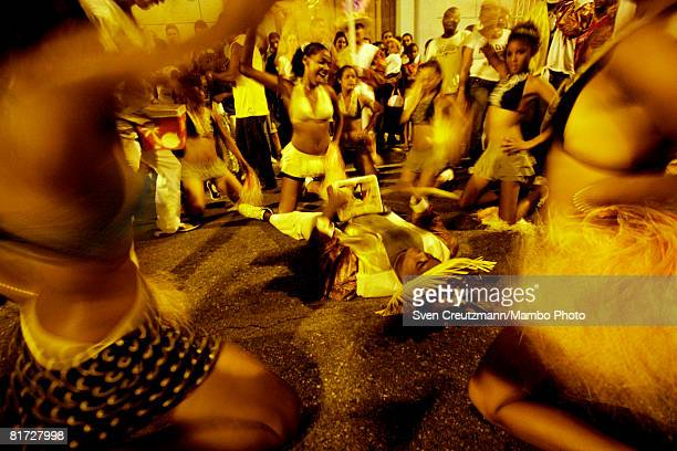 Cuban girls sway with their hips as they sit around a man who lies on the ground as part of the opening ceremony during the Camaguey carnival June 24...