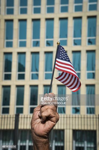A Cuban holds a little US flag in front of the US Embassy in Havana on July 20 2015 The United States and Cuba formally resumed diplomatic relations...
