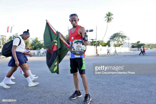 Cuban holds a photos of late Cuban Revolution leader Fidel Castro prior to a march from the Revolution square to the Santa Ifigenia cemetery as Cuba...