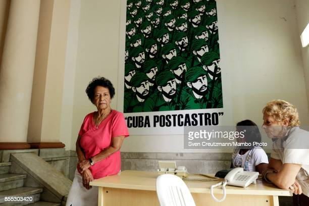 Cuban journalist and author Marta Rojas poses under a poster that shows multiple images of Fidel Castro and reads CUBA POSTCASTRO in the headquarter...