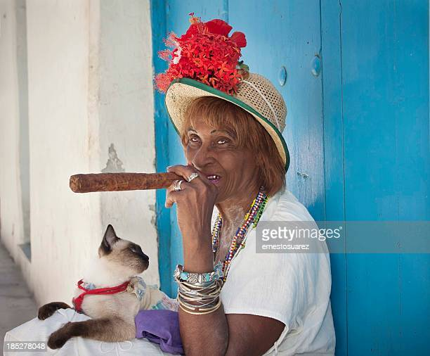 Cuban lady sitting with a cigar and cat
