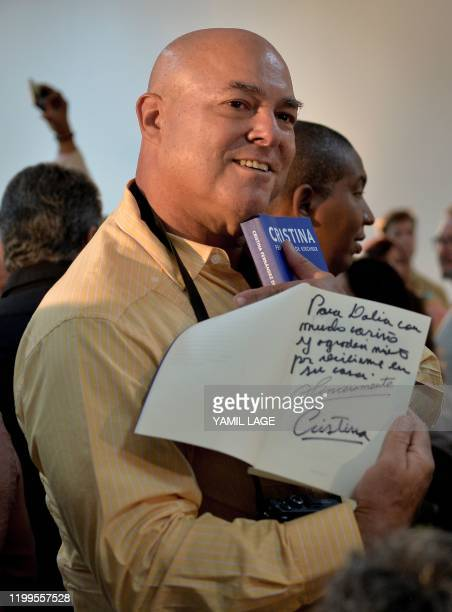 Cuban late leader Fidel Castro's son Alex Castro shows a copy of Argentine VicePresident Cristina Kirchner's book Sincerely dedicated to his mother...