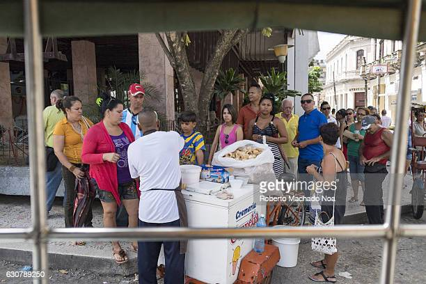Cuban lifestyle Locals and tourists flocking an Ice cream vendors cart in the Coppelia corner View from the back of motorcycle prepared to transport...