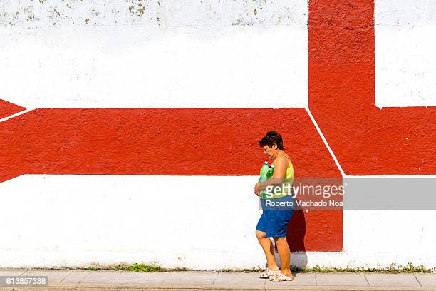 Cuban lifestyle or way of life: Woman with large plastic bottles walking in front of red patterned wall.