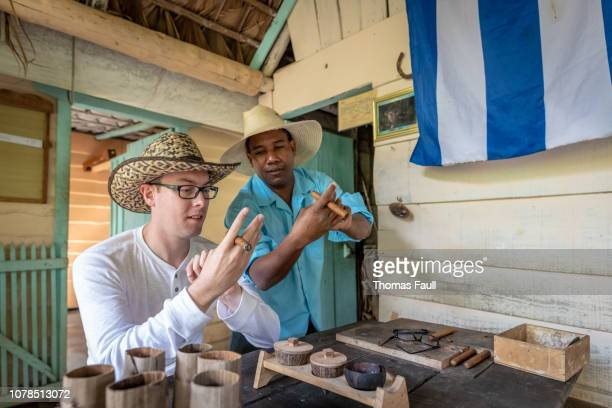 cuban man demonstrates cuban cigars to a tourist - pinar del rio stock photos and pictures