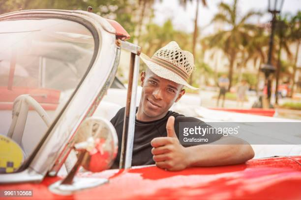 Cuban man giving Ok sign driving vintage car in Cuba Old Havana
