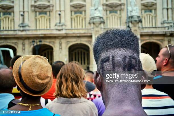 Cuban man has the word Cuba shaved in the back part of his head as he and hundreds await the coffin of Cubas late Ballet legend Alicia Alonso to be...