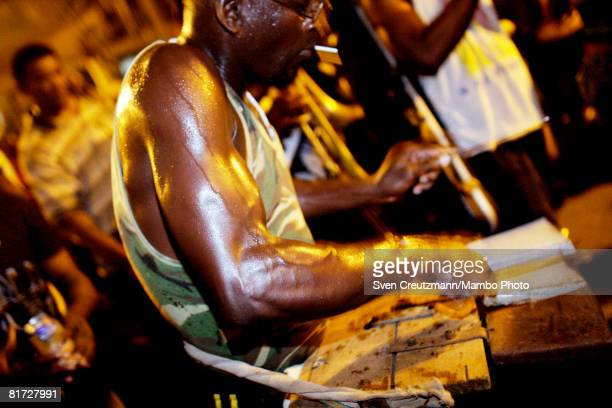 Cuban man hits his makeshift drum as conga groups march through the streets during the Camaguey carnival June 24 2008 in Camaguey Cuba The first day...