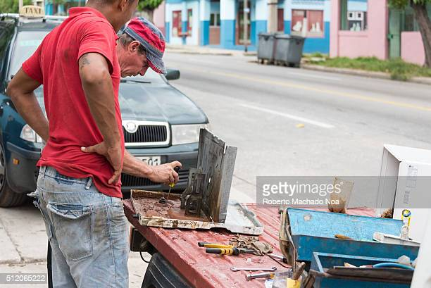 Cuban man repairing air conditioner in the street A repairer is working on AC to make it work Due to economic conditions many old equipment gets...
