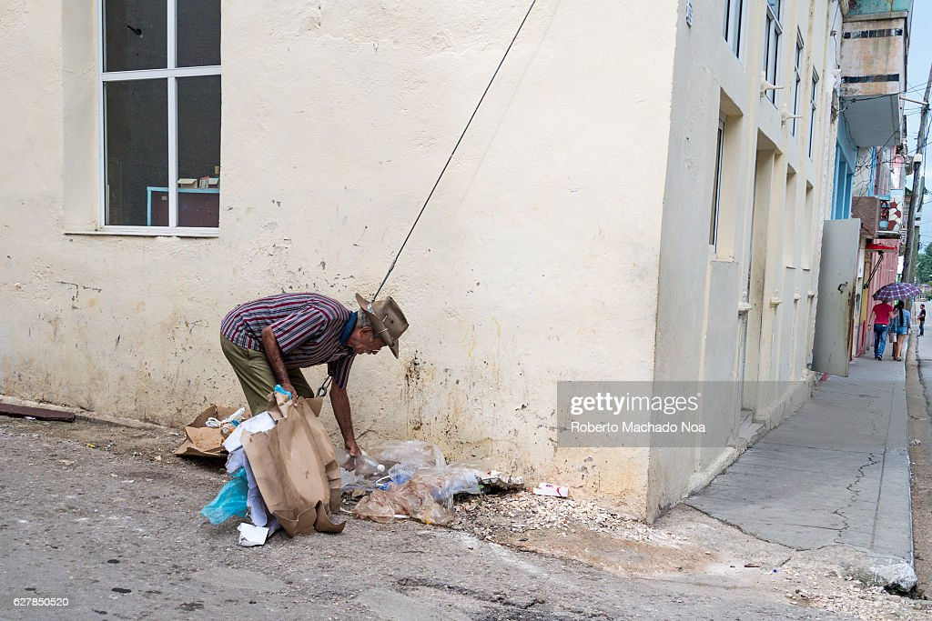 Cuban man searching cans or bottles in the garbage. Taking... : News Photo