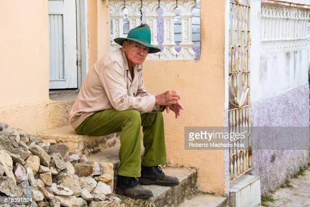 Cuban man sitting on a doorstep He wears military pants long sleeves and a straw hat The clothing is traditional for construction workers and other...