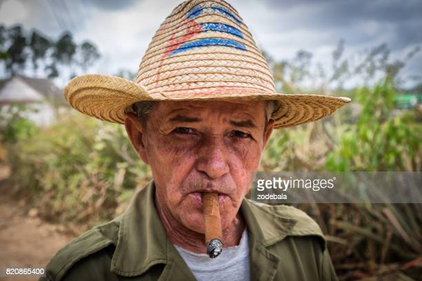 hombre cubano fumando un puro - bandera cubana fotografías e imágenes de stock