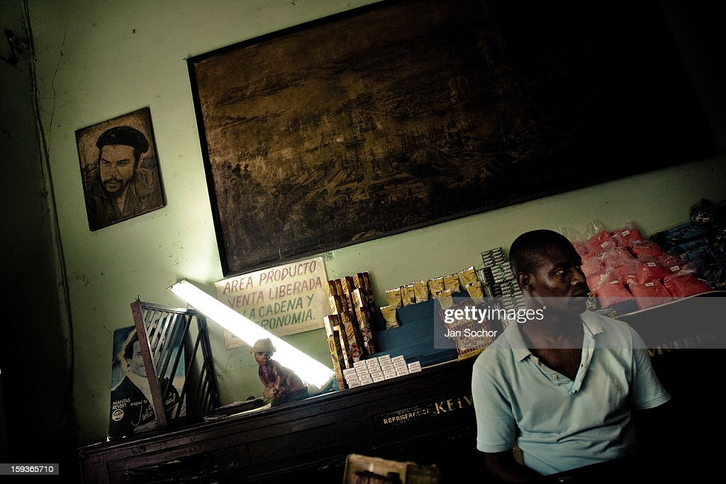 A Cuban man stands behind the shop counter under a portrait of the revolutionary leader Che Guevara, hung on the wall of a shop, in Havana, Cuba, 16 August 2008 in Havana, Cuba. During the Cuban Revolution, an armed rebellion at the end of the 1950s, most of the revolutionary leaders started as unnamed soldiers fighting from the jungle. After taking over the power, they became autocratic rulers holding almost absolute power and pursuing the opposition. For some reason Cuban people never stopped to worship Fidel Castro, Che Guevara, Raul Castro and others. Cubans hang their photos and portraits on the wall at home, shops and working places even when they don't have to.