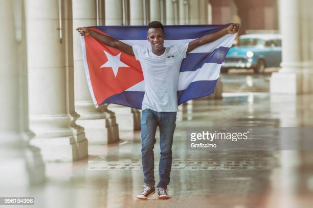 Cuban man walking with cuban flag through Old Havana