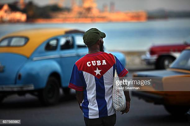 Cuban man wearing a shirt showing his national flag walks along the Malecon at sunset on December 18 2015 in Havana Cuba The Malecon is city's famed...